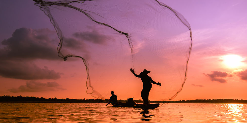 Silhouette of a fisherman throwing his net